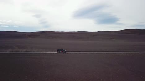 Very-good-vista-aérea-of-a-black-van-traveling-on-a-dirt-road-across-the-highland-interior-of-Iceland-1