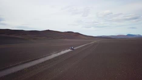 Muy-Buena-Antena-De-Una-Furgoneta-Negra-Viajando-Por-Un-Camino-De-Tierra-A-Través-Del-Interior-De-Las-Tierras-Altas-De-Islandia-2