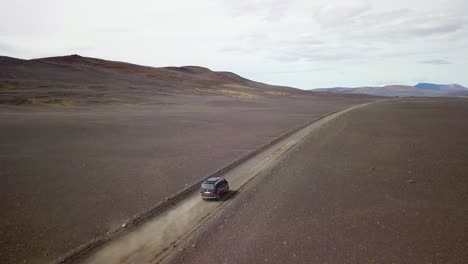 Very-good-aerial-of-a-black-van-traveling-on-a-dirt-road-across-the-highland-interior-of-Iceland-3