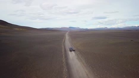 Very-good-aerial-of-a-black-van-traveling-on-a-dirt-road-across-the-highland-interior-of-Iceland-4