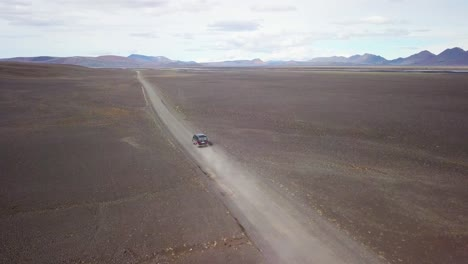 Very-good-aerial-of-a-black-van-traveling-on-a-dirt-road-across-the-highland-interior-of-Iceland-5