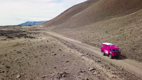 Aerial-of-a-rare-pink-Land-Rover-101-driving-through-the-outback-highlands-of-desolate-Iceland-1