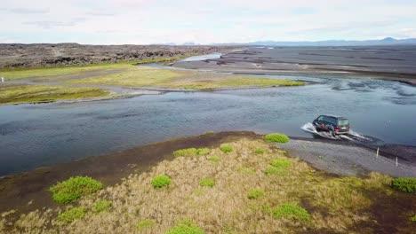 Antena-Sobre-Una-Camioneta-Negra-Conduciendo-A-Través-De-Un-Río-En-Las-Tierras-Altas-De-Islandia