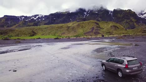 Vista-Aérea-over-a-Toyota-4x4-conduciendo-through-a-río-in-the-highlands-of-Iceland