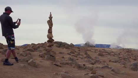 A-man-stacks-balancing-rocks-stones-near-a-geothermal-area-in-Iceland