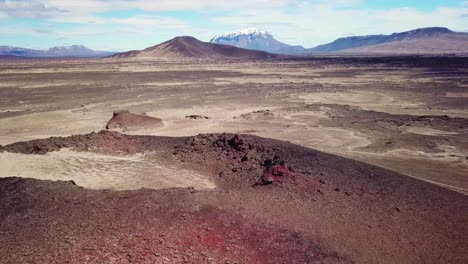 Spectacular-aerial-over-red-ash-topped-volcanoes-and-lava-flows-in-the-remote-highland-interior-of-Iceland-2