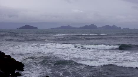 Establishing-shot-of-the-Westmann-Islands-in-Iceland-with-a-stormy-dark-sea-foreground