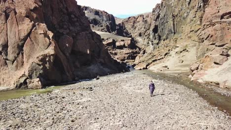 Aerial-over-a-woman-walking-into-a-deep-and-mysterious-canyon-in-Askja-central-highlands-of-Iceland