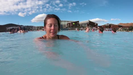 A-woman-swims-in-a-geothermal-pool-at-a-day-spa-in-Iceland