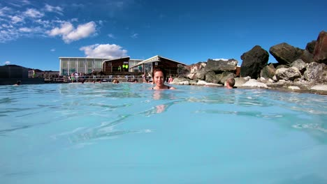 A-man-and-woman-swim-in-a-geothermal-pool-at-a-day-spa-in-Iceland-1