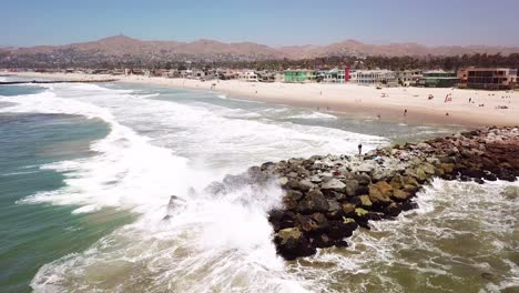 Aerial-of-a-man-fishing-off-a-breakwater-during-a-big-ocean-swell-with-large-waves-off-Ventura-harbor-California-1