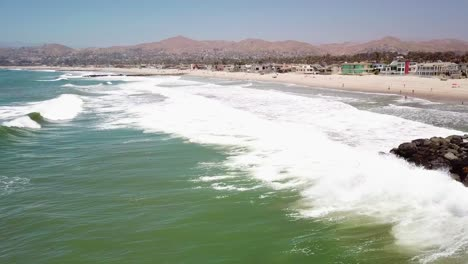 Aerial-of-a-man-fishing-off-a-breakwater-during-a-big-ocean-swell-with-large-waves-off-Ventura-harbor-California-2