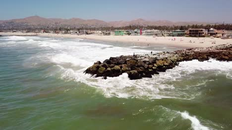 Aerial-of-a-man-fishing-off-a-breakwater-during-a-big-ocean-swell-with-large-waves-off-Ventura-harbor-California-5