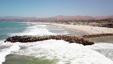 Aerial-of-a-man-fishing-off-a-breakwater-during-a-big-ocean-swell-with-large-waves-off-Ventura-harbor-California-6
