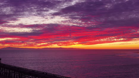An-astonishing-sunset-aerial-shot-over-a-long-pier-and-the-Pacific-Ocean-and-Channel-Islands-in-Ventura-Southern-California-1