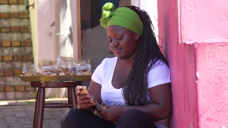 A-young-girl-looks-at-her-phone-in-the-colorful-Bo-kaap-Malay-area-of-Cape-Town-South-Africa-with-colonial-buildings-and-traffic