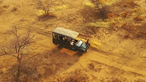 Excellent-aerial-of-a-safari-jeep-traveling-on-the-plains-of-Africa-at-Erindi-Game-Preserve-Namibia-with-native-San-tribal-spotter-guide-sitting-on-front-spotting-wildlife-2