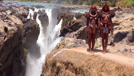 Tilt-up-from-Epupa-Falls-in-Namibia-reveals-two-Himba-tribal-woman