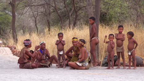 African-San-bushmen-women-children-and-tribal-natives-sit-in-a-circle-chanting-singing-and-clapping-in-a-small-village-in-Namibia