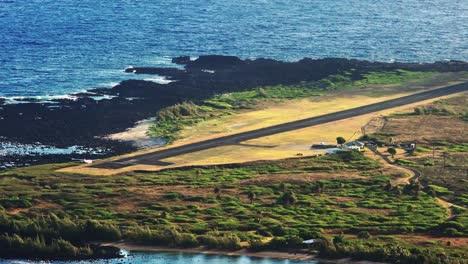 High-angle-establishing-shot-of-Kalaupapa-airport-and-small-plane-landing-on-the-island-of-Molokai-Hawaii