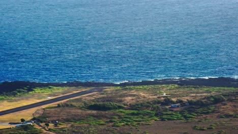 High-angle-establishing-shot-of-Kalaupapa-airport-and-small-plane-landing-on-the-island-of-Molokai-Hawaii-1