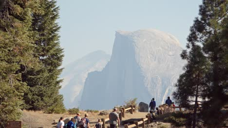 Tourists-at-a-Glacier-Point-vista-in-Yosemite-National-Park-Half-Dome-and-the-Sierra-Nevada-Mountains-in-the-distance