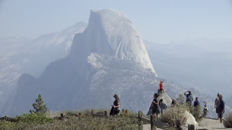 A-boy-on-a-rock-at-Glacier-Point-Yosemite-National-Park-Half-Dome-and-the-Sierra-Nevada-Mountains-in-the-distance