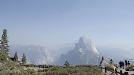 A-boy-on-a-rock-at-Glacier-Point-Yosemite-National-Park-Half-Dome-and-the-Sierra-Nevada-Mountains-in-the-distance-1