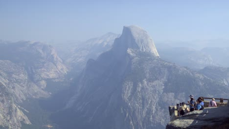 Tourists-at-a-Glacier-Point-vista-in-Yosemite-National-Park-Half-Dome-and-the-Sierra-Nevada-Mountains-in-the-distance-1