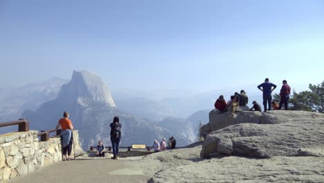 Tourists-at-a-Glacier-Point-vista-in-Yosemite-National-Park-Half-Dome-and-the-Sierra-Nevada-Mountains-in-the-distance-2