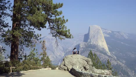 A-couple-takes-a-selfie-at-Washburn-Point-with-Half-Dome-and-High-Sierra-Mountain-Range-Yosemite-National-Park-CA