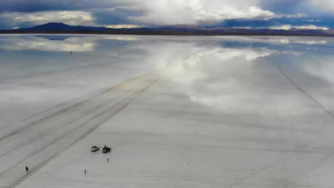 Aerial-of-people-gathering-on-the-Uyuni-salt-flats-lake-with-perfect-reflections-in-Bolivia-1