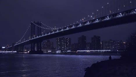 U-Bahnen-überqueren-Die-Brooklyn-Bridge-Mit-Der-Skyline-Von-New-York-City-Im-Hintergrund-Bei-Nacht-1