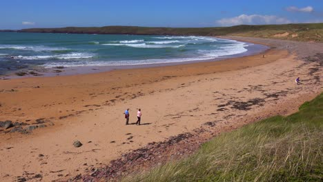 People-walk-along-a-beautiful-beach-on-the-coast-of-Southern-Wales