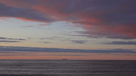 A-very-distant-cargo-ship-on-the-horizon-at-sunset