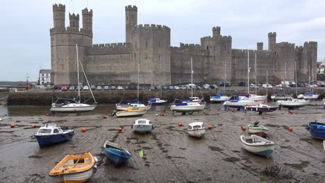 The-beautiful-Caernarfon-Castle-at-low-tide-with-beached-boats-in-Wales