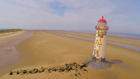 A-magnificent-aerial-shot-of-the-Point-of-Ayr-lighthouse-in-Wales-with-weathered-fence-in-foreground-1
