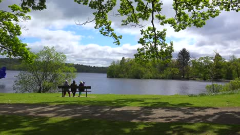 People-sit-on-a-bench-enjoying-the-scenery-at-Loch-Lomand-Scotland