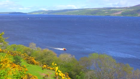 An-establishing-shot-of-Loch-Ness-Scotland-with-speedboat-passing