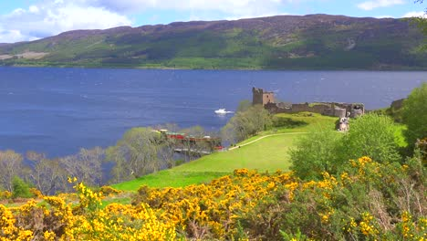 An-establishing-shot-of-Loch-Ness-castle-Scotland-with-speedboat-passing