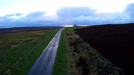 Aerial-over-a-beautiful-road-through-Scotland-or-Ireland-after-the-rain-with-distant-abandoned-stone-building