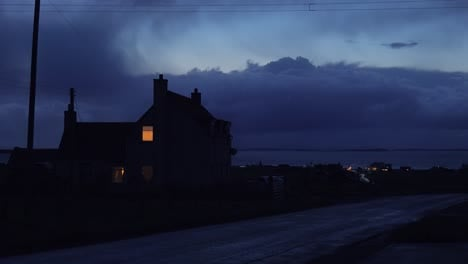 A-light-shines-in-the-upstairs-bedroom-of-a-lonely-house-in-the-countryside-at-night