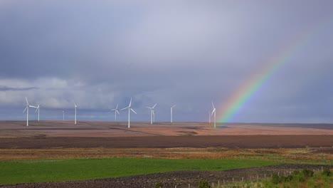 A-beautiful-rainbow-forms-near-wind-generation-windmills-in-Northern-Scotland-1