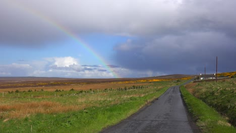 A-beautiful-rainbow-forms-along-a-one-lane-road-in-Scotland-or-Ireland