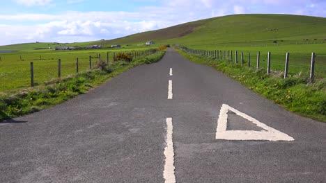 Una-Carretera-Vacía-Atraviesa-Campos-Verdes-Brillantes-En-Las-Islas-Orkney-De-Escocia-