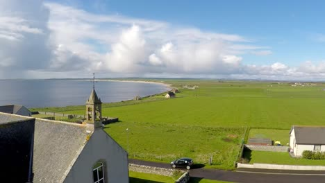 An-aerial-shot-over-a-pretty-church-along-the-abandoned-coastline-of-Northern-Scotland