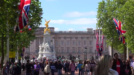 Establishing-shot-of-Buckingham-Palace-London-with-British-flags-and-crowds-of-tourists
