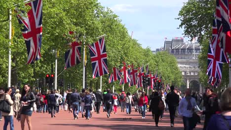 Pedestrians-walk-on-the-Mall-near-Buckingham-Palace-London-with-British-flags-flying