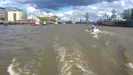 A-POV-shot-along-the-Thames-River-of-the-Tower-of-London-Bridge-in-distance