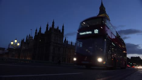 Traffic-passes-in-front-of-Big-Ben-and-Houses-Of-Parliament-in-London-England-at-night